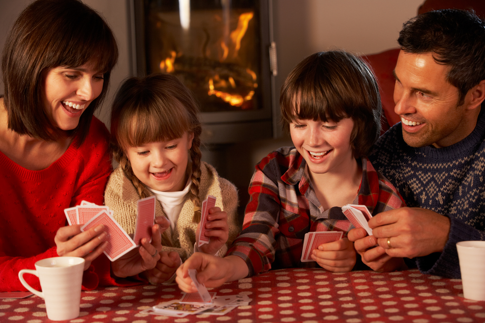 Family playing card games by the fireplace